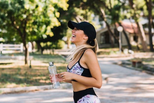 Vista lateral de una mujer joven feliz que se coloca en el parque que sostiene la botella de agua
