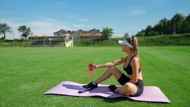 Vista lateral de la mujer joven en forma sosteniendo una botella con agua, sentado en la alfombra, campo del estadio en un día soleado de verano. chica atlética con traje deportivo que descansan sobre la hierba verde. concepto de deporte, entrenamiento.