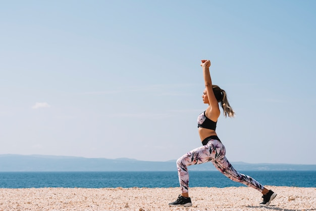 Vista lateral de una mujer joven haciendo ejercicios de estiramiento cerca de la playa