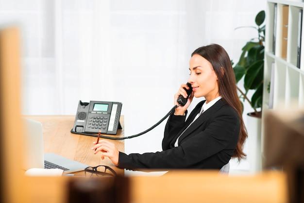 Vista lateral de una mujer joven con lápiz en la mano hablando por teléfono