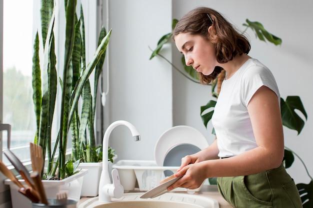 Vista lateral, mujer joven, lavar platos