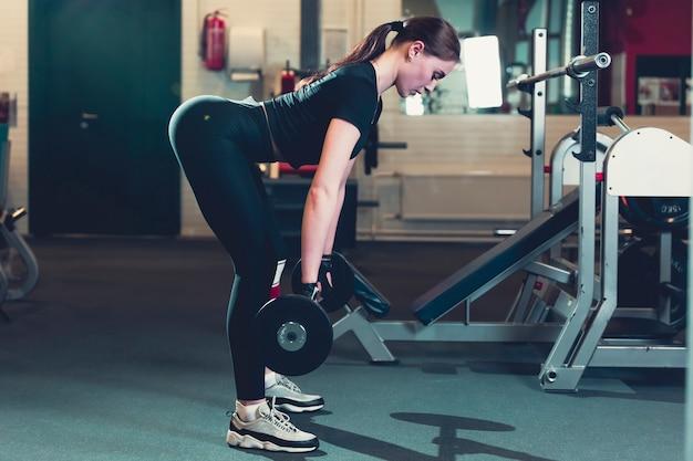 Vista lateral de una mujer joven levantando peso en el gimnasio