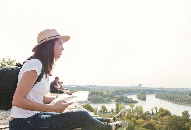 Vista lateral, de, mujer joven, con, mapa, mirar la vista