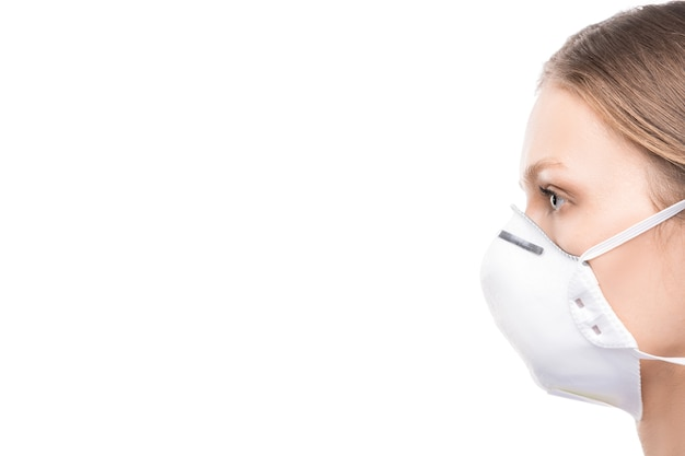 Vista lateral de la mujer joven con máscara protectora de pie en aislamiento durante el período de virus peligroso propagado por todo el mundo