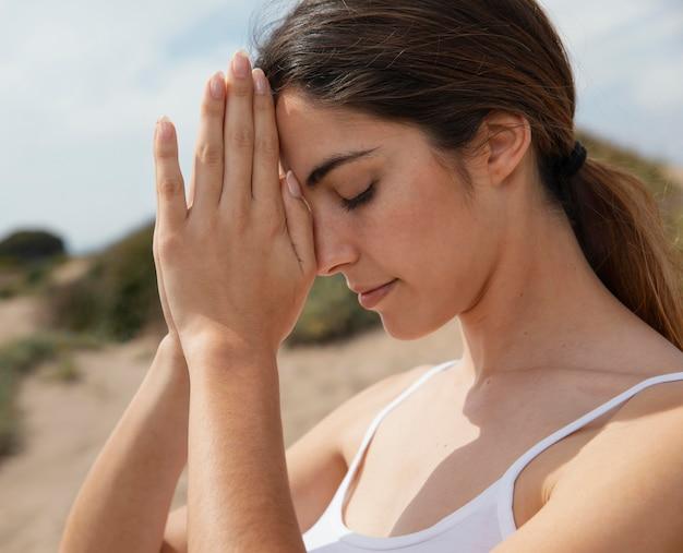 Vista lateral, mujer joven, meditar