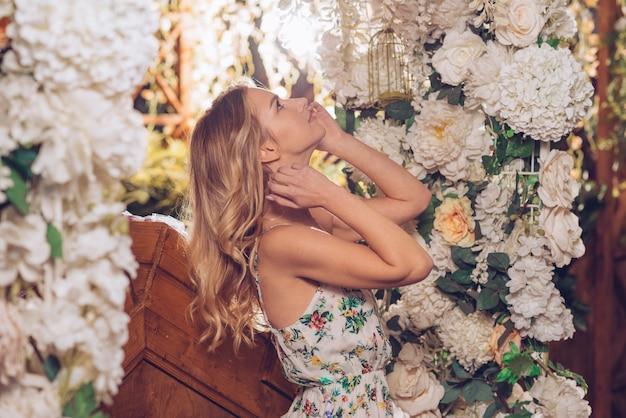 Vista lateral de una mujer joven mirando hacia arriba en la decoración de flores blancas en el jardín