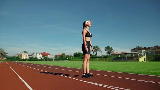Vista lateral de la mujer joven muscular cansada con gorra blanca y ropa deportiva negra que descansan durante los ejercicios de calentamiento en el estadio. colocar chica con los ojos cerrados sosteniendo saltar la cuerda al aire libre.
