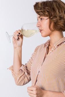 Vista lateral de una mujer joven que bebe el vino aislado en el fondo blanco
