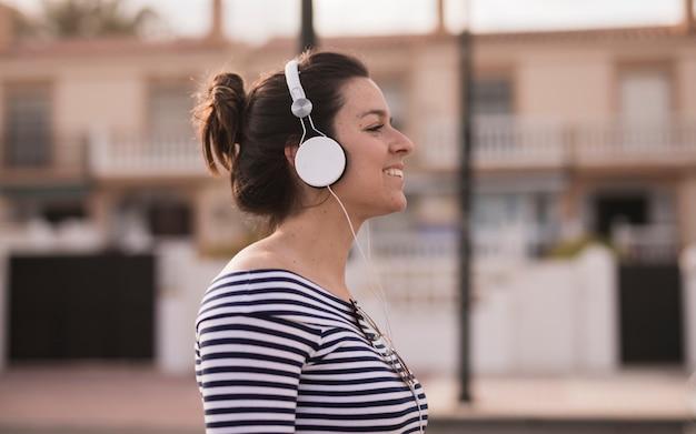 Vista lateral de una mujer joven que disfruta de la música que escucha en el auricular
