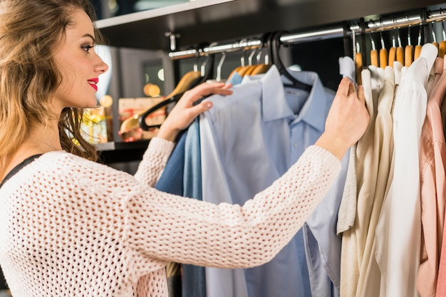 Vista lateral de una mujer joven que elige la ropa en el estante en una sala de exposición