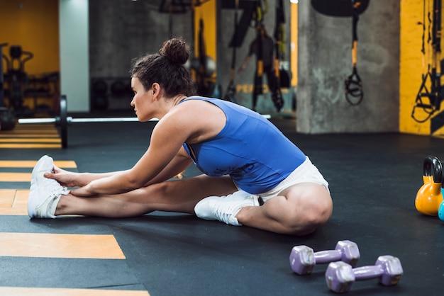 Vista lateral de una mujer joven que estira su pierna en gimnasio
