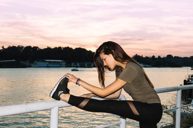 Vista lateral de una mujer joven que estira su pierna