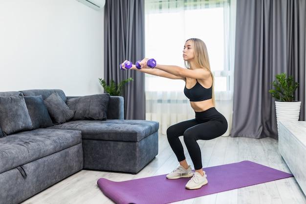 Vista lateral de la mujer joven que hace sentadillas en la estera del ejercicio en una sala de estar.