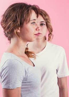 Vista lateral de la mujer joven que está parada delante de su hermana contra fondo rosado