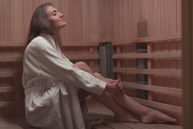 Vista lateral de la mujer joven que se sienta en banco de madera en sauna