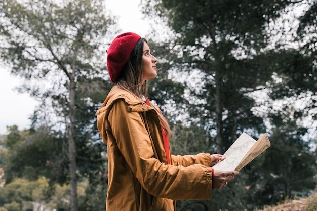 Vista lateral de una mujer joven que sostiene el mapa en la mano de pie en el bosque