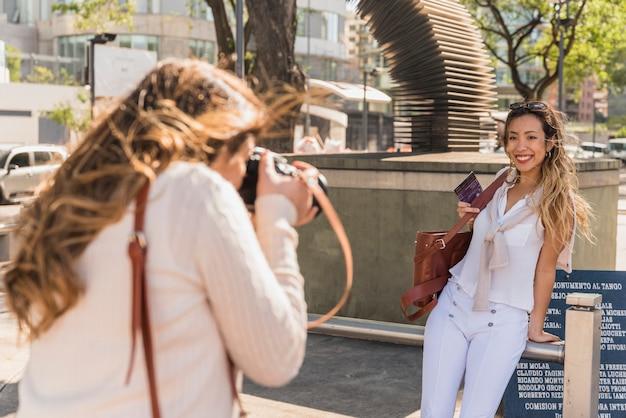Vista lateral de una mujer joven que toma una foto de su amiga apoyada en una barandilla