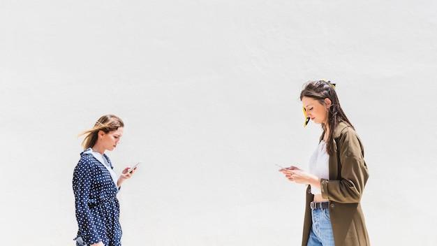 Vista lateral de la mujer joven que usa smartphone contra el contexto blanco