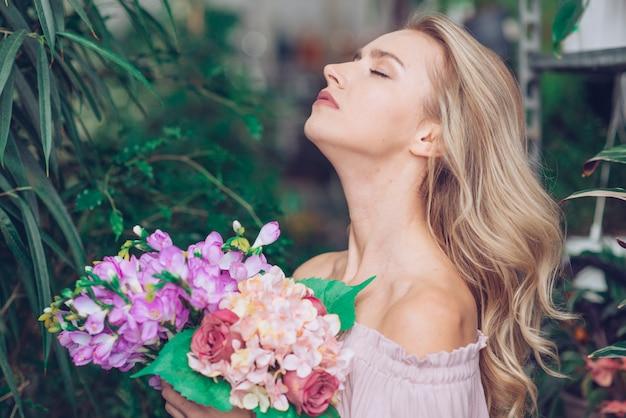 Vista lateral de una mujer joven relajada que se coloca en el jardín que sostiene el ramo colorido de la flor