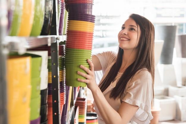 Vista lateral de una mujer joven sonriente que arregla las plantas florecientes en estante