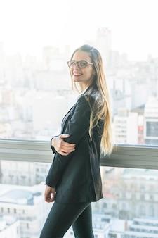 Vista lateral de la mujer joven sonriente que se coloca cerca de la ventana
