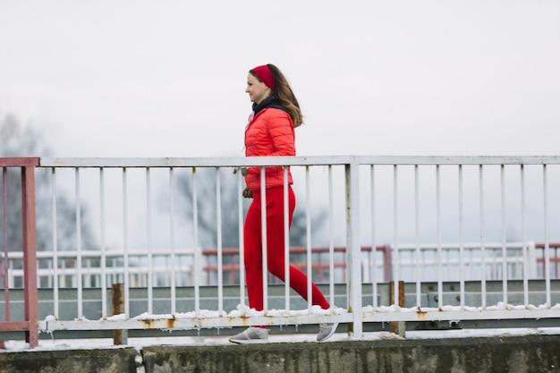 Vista lateral de la mujer joven sonriente que corre detrás de la barandilla en invierno