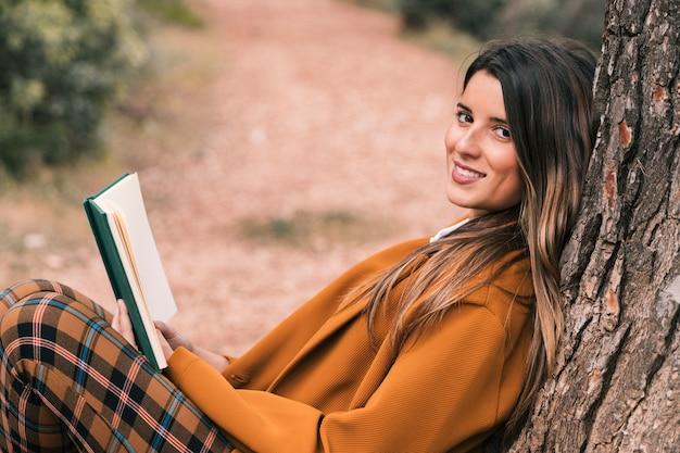 Vista lateral de una mujer joven sonriente sentada bajo el árbol sosteniendo un libro en la mano mirando a la cámara