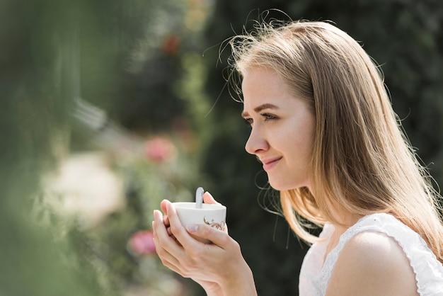Vista lateral de una mujer joven sosteniendo una taza de café en dos manos