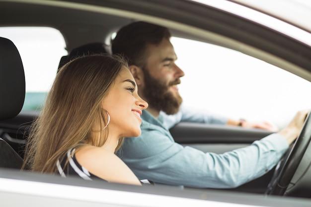 Vista lateral de una mujer joven con su novio viajando en el coche