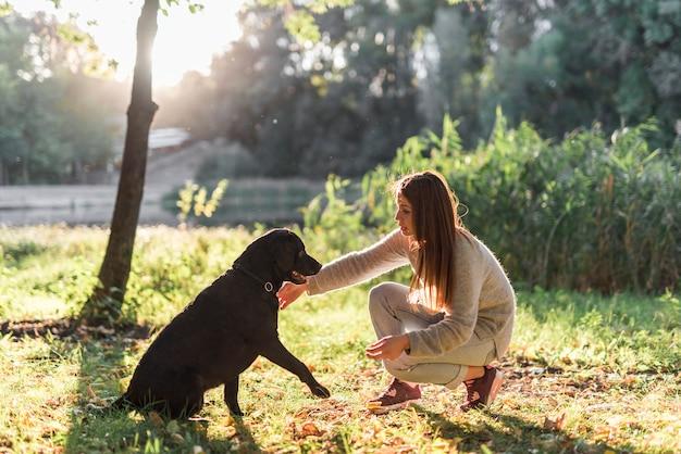 Vista lateral de la mujer joven con su perro labrador en el parque