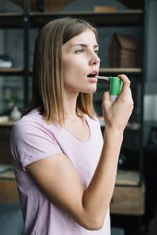 Vista lateral de una mujer joven usando spray para la garganta