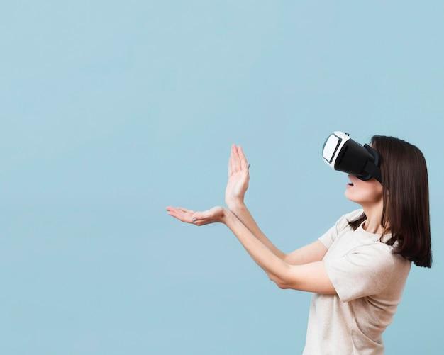 Vista lateral de la mujer jugando mientras usa casco de realidad virtual con espacio de copia