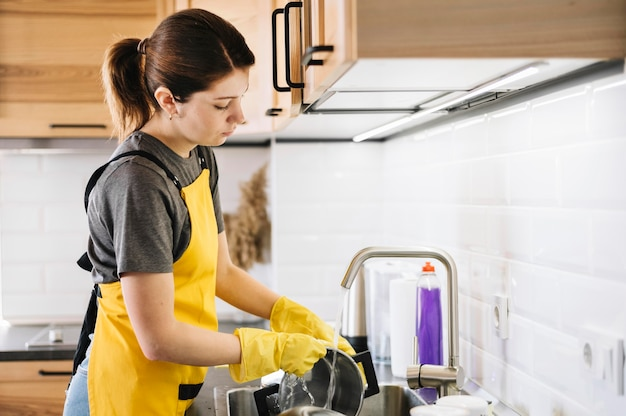 Vista lateral mujer lavando platos