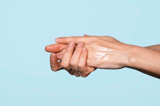 Vista lateral mujer lavándose las manos aisladas en azul