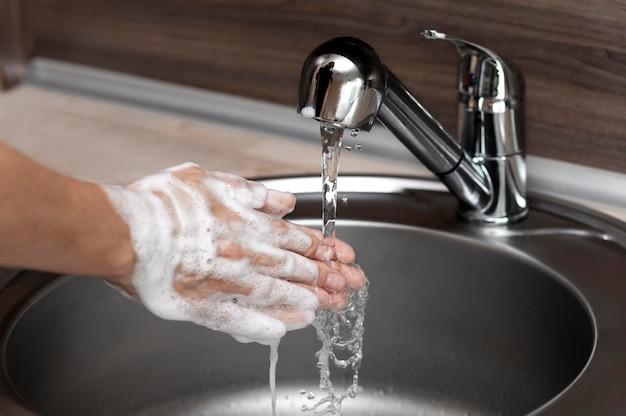 Vista lateral de la mujer lavándose las manos en un fregadero