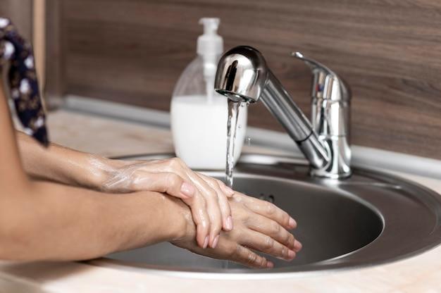 Vista lateral, mujer, lavarse las manos