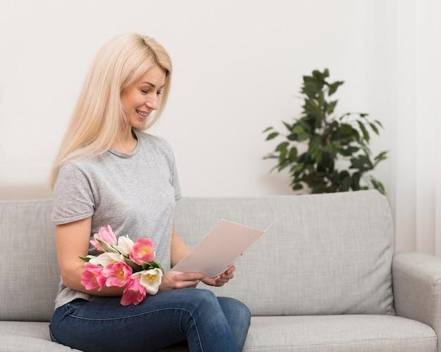 Vista lateral mujer leyendo tarjetas de felicitación
