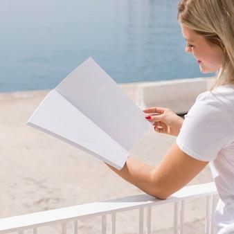Vista lateral, de, mujer, libro de lectura, por, el, lago