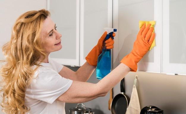 Vista lateral de la mujer limpiando los gabinetes de la cocina