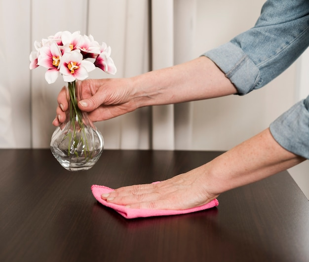 Vista lateral de la mujer limpiando la mesa con un trapo