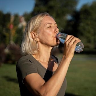 Vista lateral, de, mujer madura, agua potable, aire libre