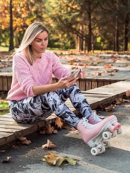 Vista lateral de la mujer en mallas y patines tomando selfie