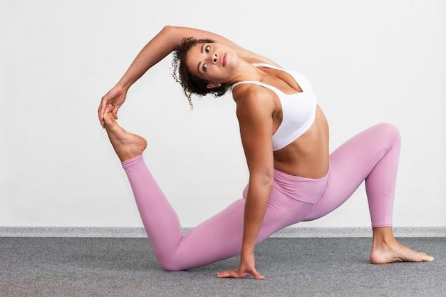 Vista lateral mujer manteniendo una pierna arriba
