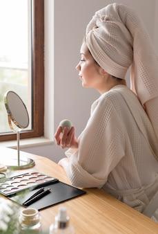 Vista lateral mujer maquillaje con esponja
