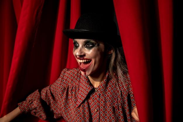Vista lateral de la mujer de maquillaje de halloween riendo
