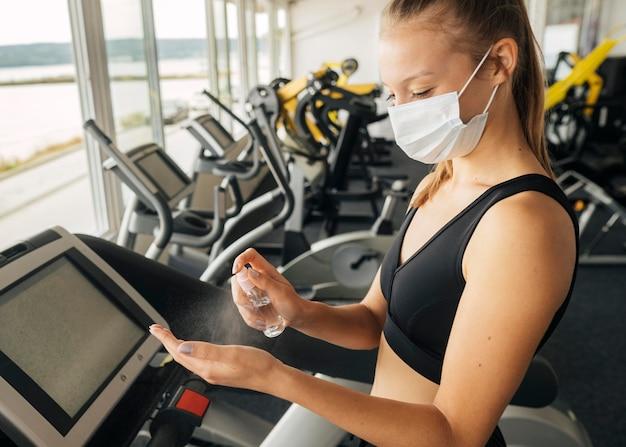 Vista lateral de la mujer con máscara médica en el gimnasio con desinfectante de manos