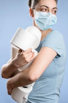 Vista lateral de la mujer con máscara médica con múltiples rollos de papel higiénico