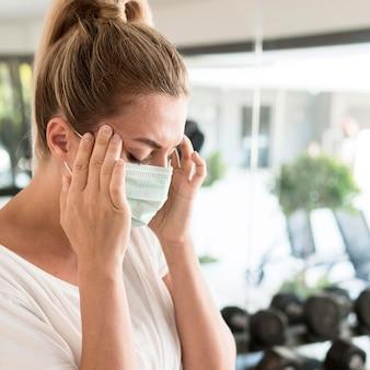 Vista lateral de la mujer con máscara médica que tiene dolor de cabeza mientras está en el gimnasio