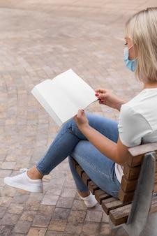 Vista lateral de la mujer con máscara médica sentada en un banco al aire libre y libro de lectura
