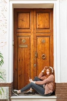Vista lateral de la mujer con mascarilla al aire libre y auriculares Foto gratis